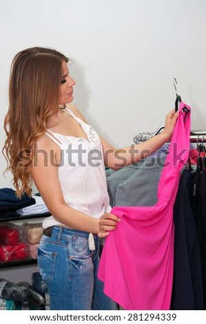 Beautiful teenage girl looking pink dress in a boutique - stock photo