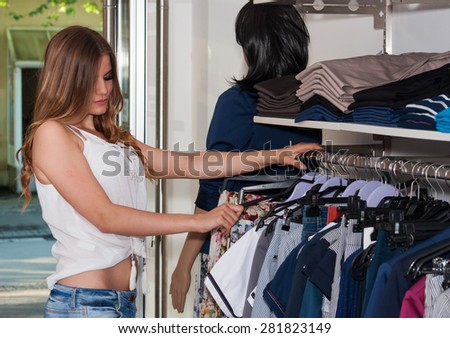 Beautiful teenage girl looking wardrobe in a boutique - stock photo