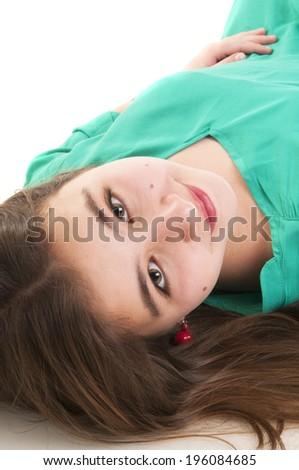 Beautiful teenage girl lying on the floor isolated on white background - stock photo