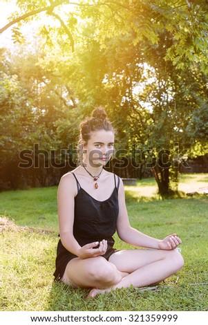 beautiful teenage girl meditates in nature - stock photo