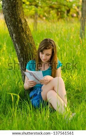 Beautiful teenage girl reading letter while sitting under the tree on sunny spring day.