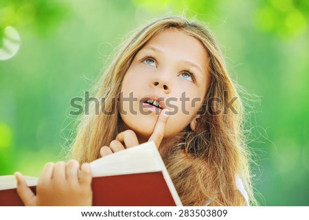Beautiful teenage girl reading red book, against green of summer park. - stock photo
