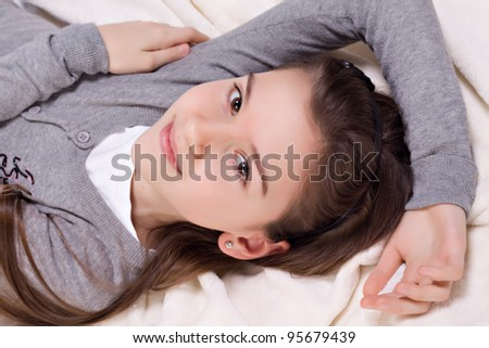 Beautiful teenage girl resting on the bed studio shot - stock photo