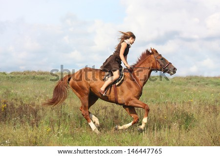 Beautiful teenage girl riding horse at the field in summer - stock photo