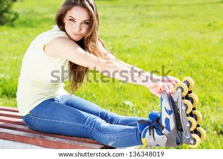 Beautiful teenage girl rollerskating in park - stock photo