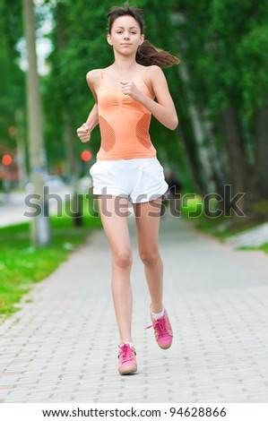 Beautiful teenage girl running in green park on sunny summer day