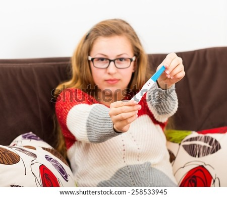 Beautiful teenage girl showing the cause of her confusion,  positive pregnancy test. - stock photo