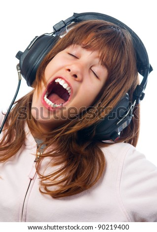 Beautiful teenage girl sings while listening to the music through headphones.