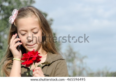 beautiful teenage girl talking on the phone and holding a red rose