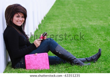 Beautiful teenage girl talking on the phone outside - stock photo