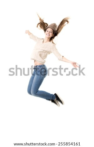 Beautiful teenage girl with broad happy smile jumping with joy, dancing, wearing jeans, jersey and knitted hat, isolated - stock photo