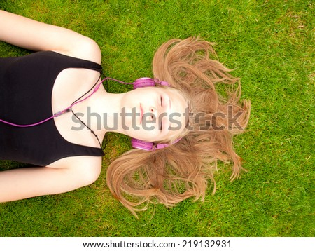 Beautiful Teenage Girl with headphones lying on her back in the green grass listening to music - stock photo