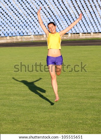 Beautiful teenage sport girl running on the grass.