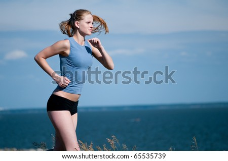 Beautiful teenage sport woman running in sea coast on sunny summer day - stock photo