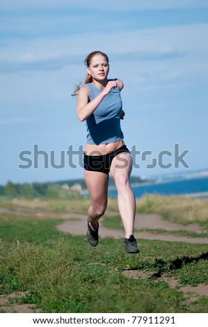 Beautiful teenage sport woman running in sea coast on sunny summer day - stock photo