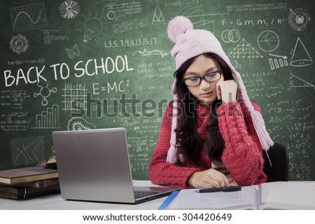 Beautiful teenage student wearing warm clothes and back to school, studying in the class with laptop and textbooks - stock photo