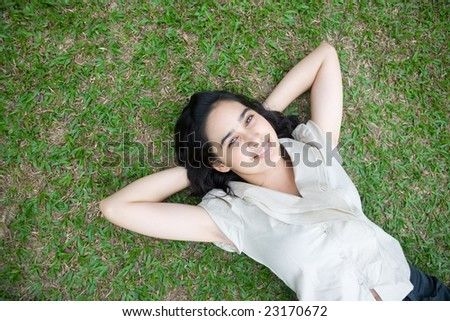 Beautiful teenage woman lying on grass in outdoor park