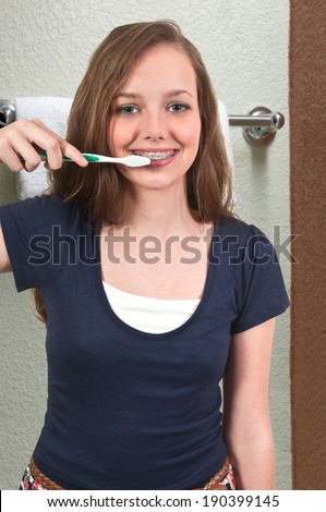 Beautiful teenage woman practicing good oral dental care by brushing her teeth - stock photo