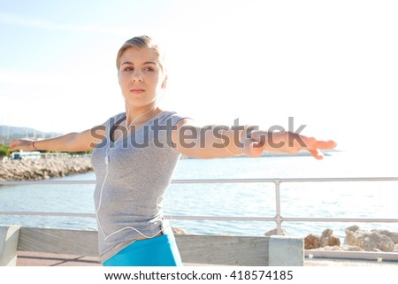 Beautiful teenager caucasian girl stretching doing sport in a sunny flare nature outdoors by the sea, using technology to listen to music. Adolescent sport lifestyle in coastal sea location, exterior. - stock photo