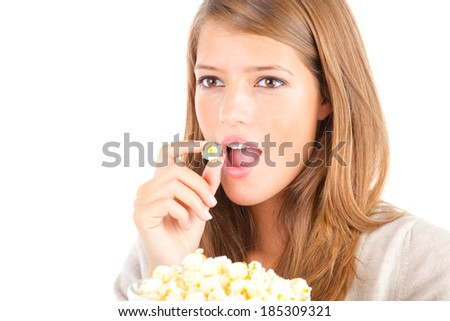 Beautiful teenager eating popcorn, studio shot, isolated on white