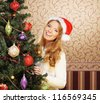 Beautiful teenager girl decorating the Christmas tree - stock photo