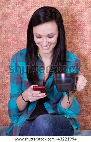 Beautiful Teenager Girl Drinking Coffee at Home while Texting - stock photo