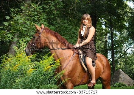 Beautiful teenager girl in brown dress riding brown horse in the park
