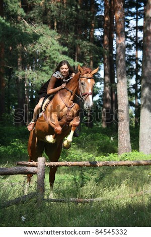 Beautiful teenager girl in dress riding chestnut horse and jumping over wooden fence - stock photo