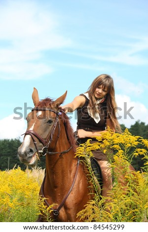 Beautiful teenager girl in dress riding chestnut horse at the field with yellow flowers