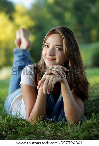 beautiful teenager girl lying in a sunny spring park smiling summer nature