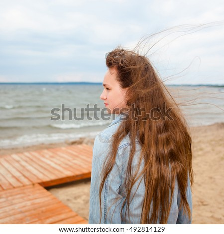 beautiful teenager girl on a windy autumn beach. portrait of a relaxed harmonious teen girl