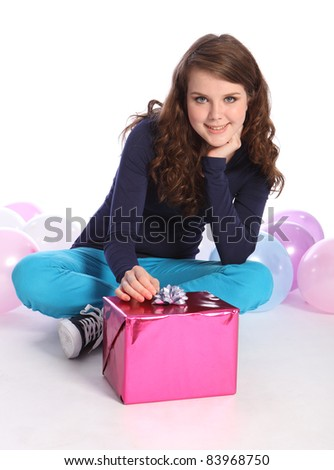 Beautiful teenager girl with bright blue eyes celebrates happy occasion with a birthday present wrapped in pink gift paper, sitting among party balloons with cheerful smile.