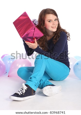 Beautiful teenager girl with bright blue eyes celebrates happy occasion with a surprise birthday present wrapped in pink gift paper, sitting among party balloons.