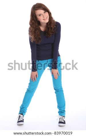 Beautiful teenager girl with bright blue eyes has fun in studio standing wearing blue jeans and navy long sleeved top and blue trainers. She has long brown hair.