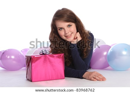 Beautiful teenager girl with bright blue eyes lying on the floor among party balloons with lovely happy smile and a birthday present wrapped in pink paper.