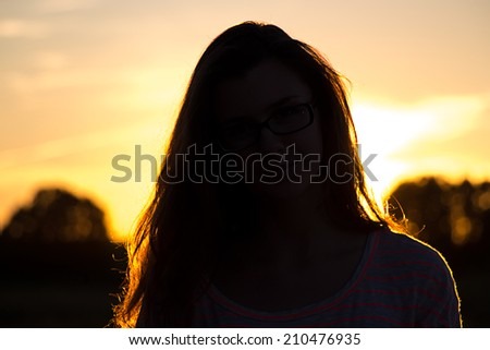 Beautiful teenager girl with glasses in the light of sunset - stock photo