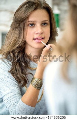 beautiful teenager girl with lip gloss front of mirror - stock photo