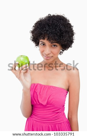 Beautiful teenager holding a green apple while looking at the camera - stock photo