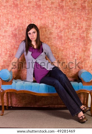 Beautiful Teenager Looking at the Camera Sitting on an Antique Couch