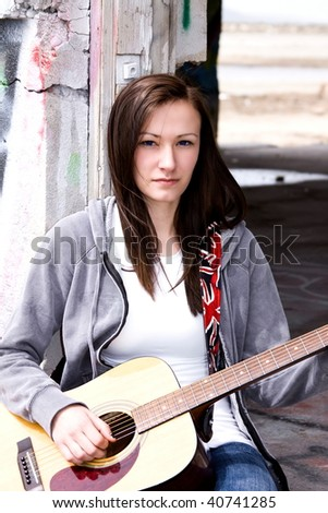 Beautiful Teenager Playing Guitar in an old abandoned Building - stock photo
