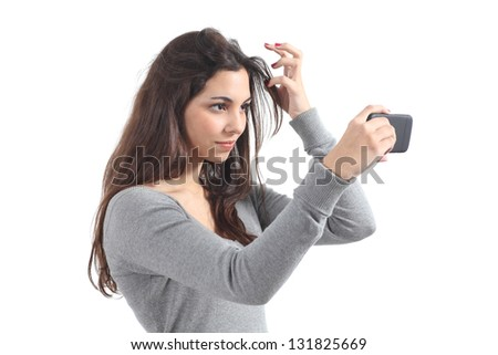 Beautiful teenager primping her hair using her phone like a mirror - stock photo