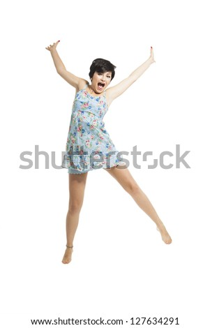 Beautiful teenager with a blue dress dancing and jumping, isolated over white background - stock photo