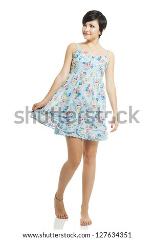 Beautiful teenager with a blue dress dancing and jumping, isolated over white background