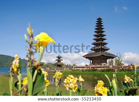 Beautiful temple on lake in extinct volcano crater with yellow flowers in the foreground - stock photo