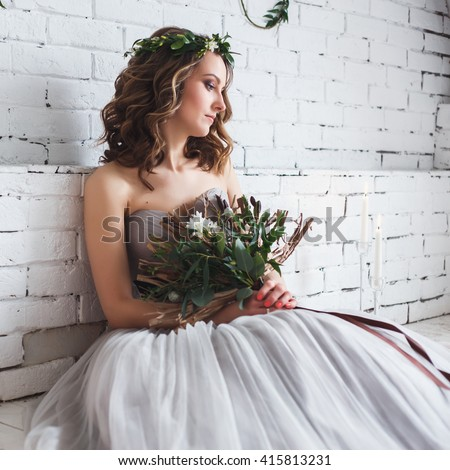 Beautiful tender bride holding creative wedding bouquet over green ecological style decor