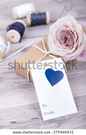 Beautiful tender flower rose with card on wooden background with space for text  Valentines Day background  mothers Day