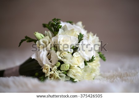 Beautiful tender fresh bridal wedding bouquet of white roses and creamy tulips with green leaves laying on light background decorative accessory for bride on marriage closeup indoor, horizontal photo  - stock photo