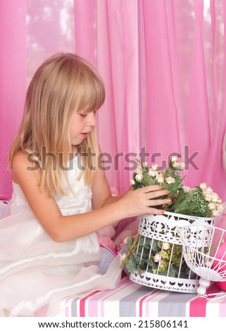 Beautiful tender girl in white festive dress holds bouquet of flowers. Over pink background. - stock photo