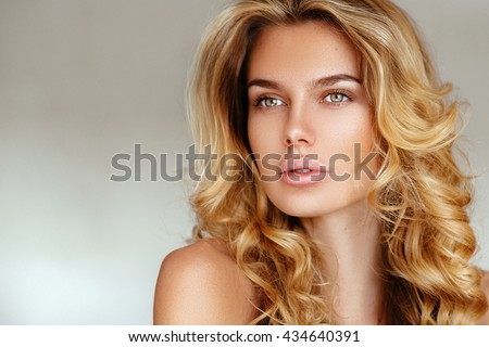 beautiful, tender, sexy blonde girl with long hair and puffy lips without makeup posing in pink lingerie on a white background. soft focus, space for text - stock photo