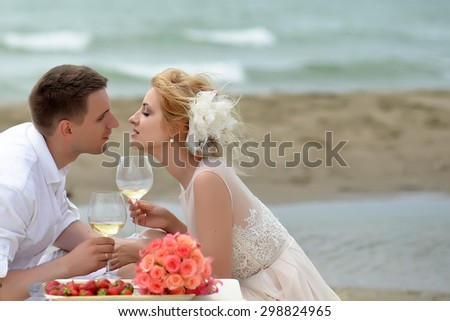 Beautiful tender wedding couple of young man and woman sitting on ocean beach shore at table with rose bouquet red strawberry kissing and drinking white wine from glasses copyspace, horizontal picture - stock photo